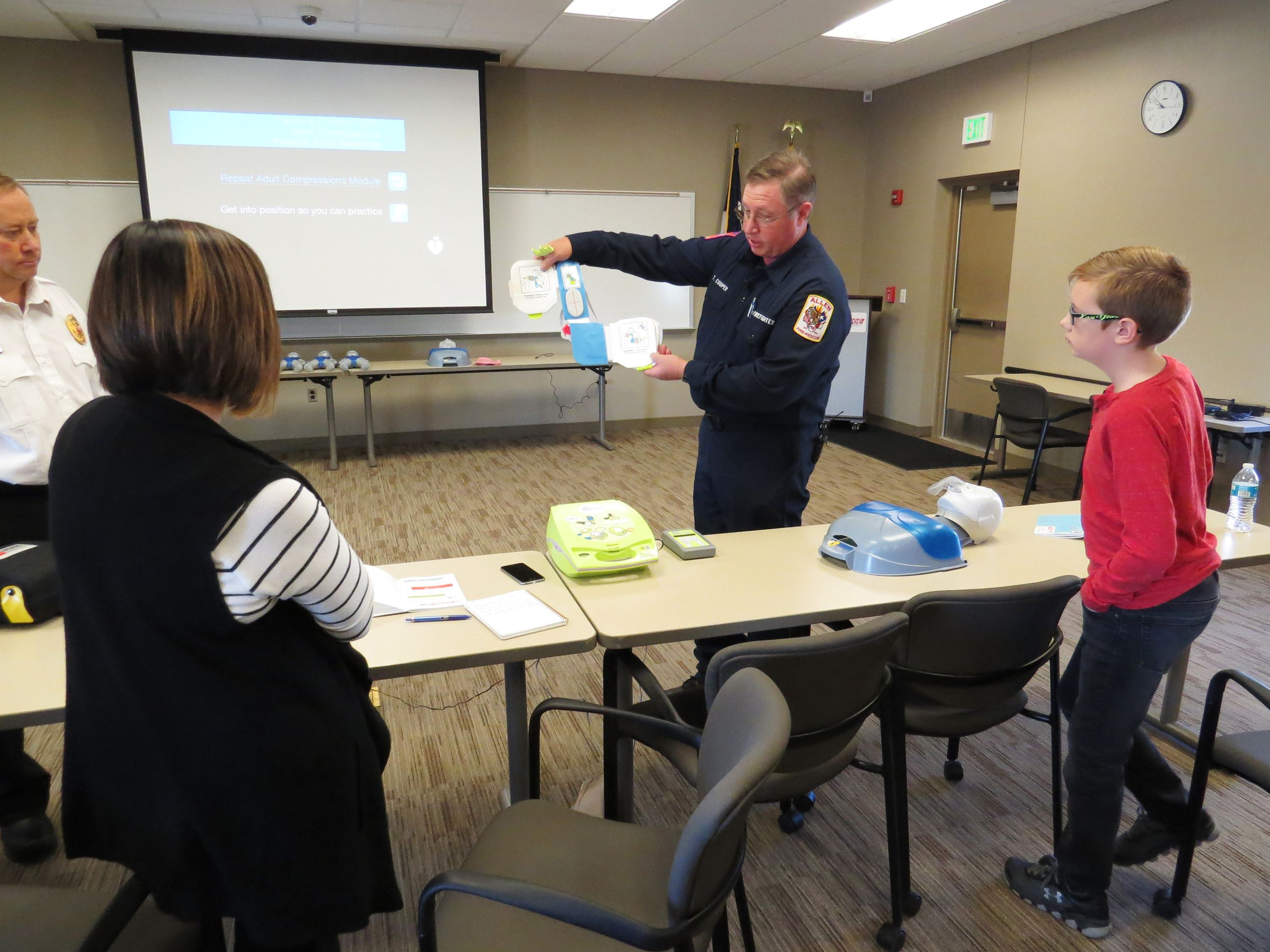 Photo of a firefighter standing in a classroom holding up two AED devices while participants watch.