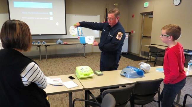Fire department staff member holding an AED device in the front of a classroom while participants wa