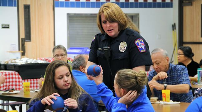 female police officer distributing foam footballs to teens sitting in cafeteria