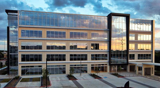 five-story glass-walled office building at sunset