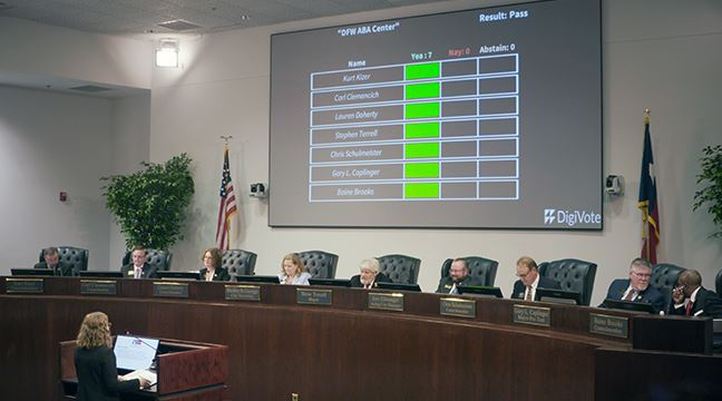 council members seated in front of digital screen during public meeting