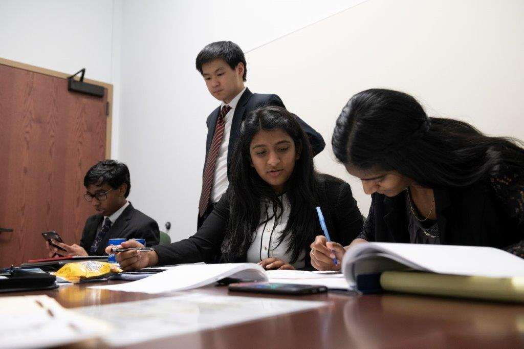 teenagers dressed in business attire review paperwork around a large wooden table