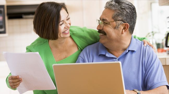 older couple looking at laptop and smiling at each other