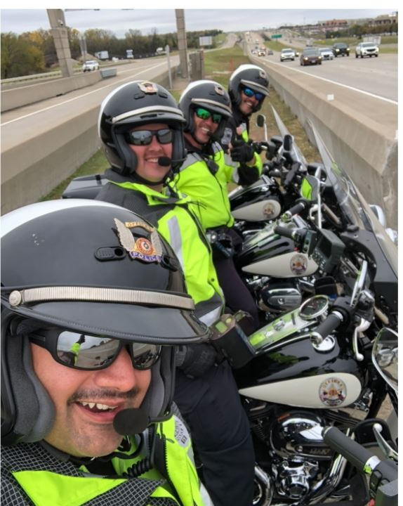 motorcycle officers lined up in highway median