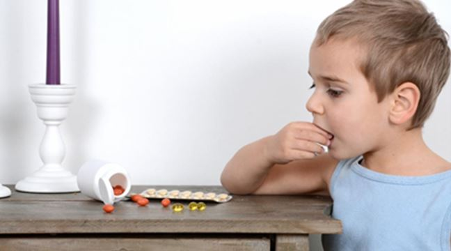 Image: Unsupervised child eating vitamins off a table