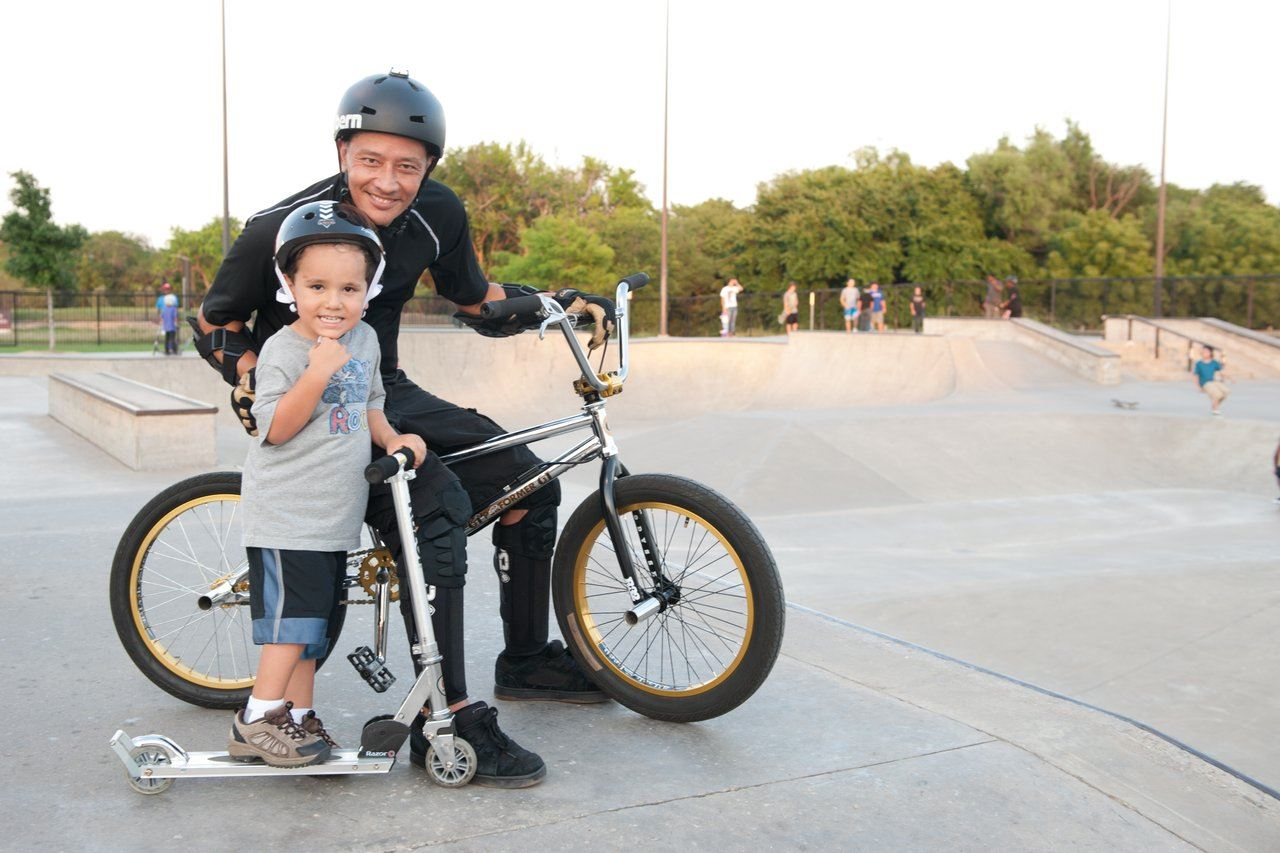 father and son riding scooters at a skate park