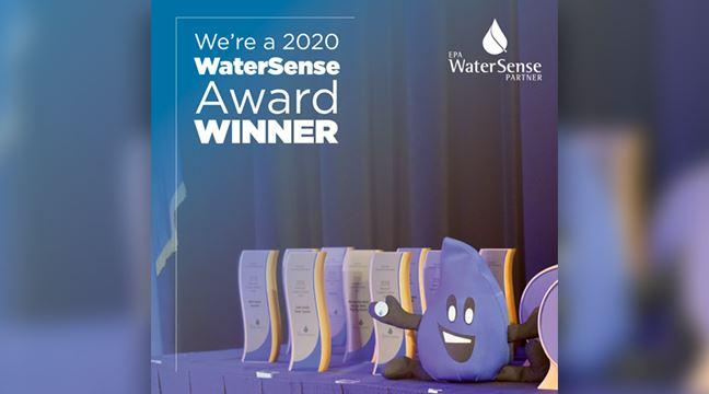 glass awards arranged next to plush toy water drop