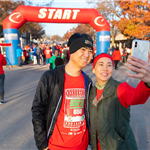 Man and woman taking a selfie at a race starting line