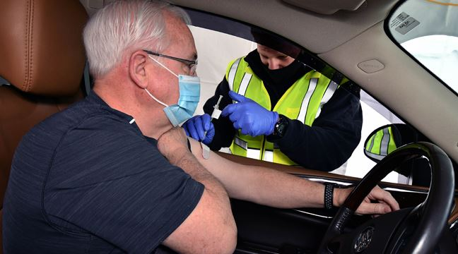 man sitting in vehicle receiving COVID-19 vaccine from an Allen firefighter