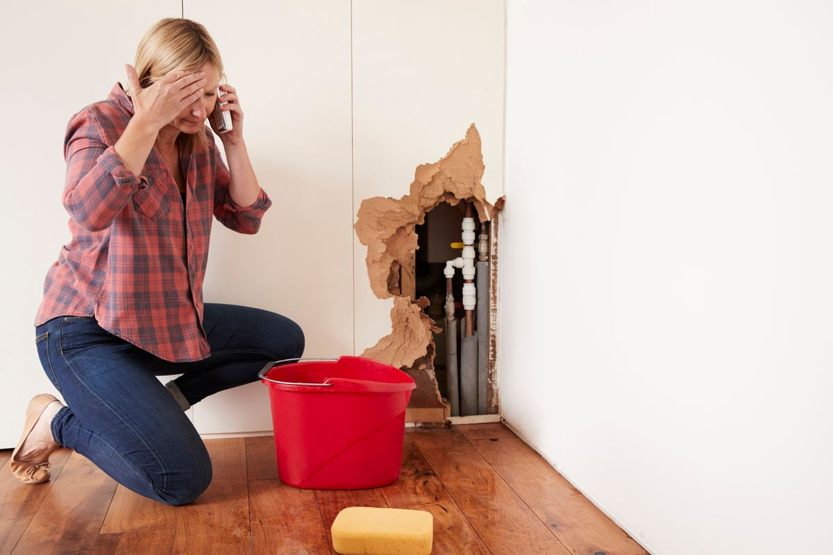 woman on the phone kneeling next to crumbled drywall and flooded floor