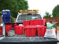pickup truck filled with red HHW bins