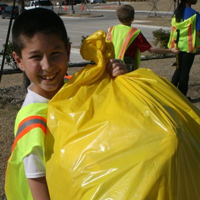 child holding large yellow bag of collected litter