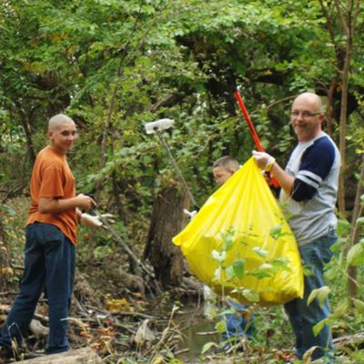 family collecting litter in the woods