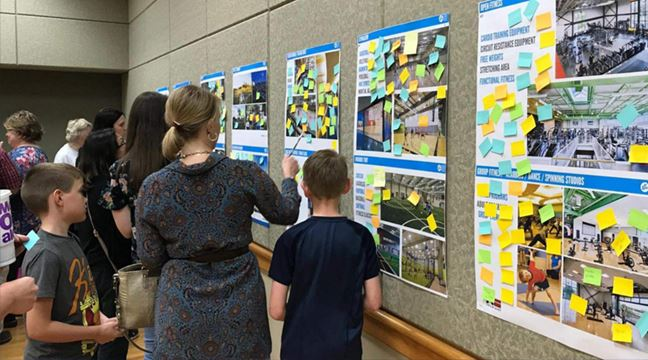 Woman and children standing in front of printed displays covered in Post-It notes